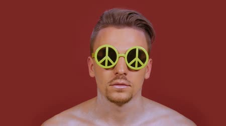 bordeauxdog : Stylish guy in funny sunglasses with peace sign looks right into the frame on a burgundy background. Portrait of young man with a bright make-up