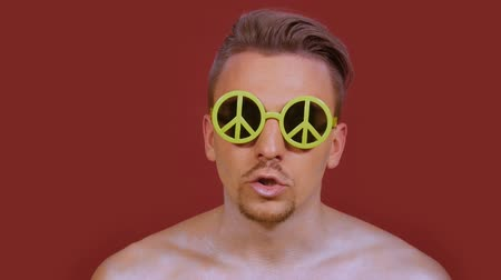 rapper : Stylish beatboxer guy in funny sunglasses with peace sign creates rhythms and looks straight into the frame on a burgundy background. A young man performing a beatbox with a bright make-up