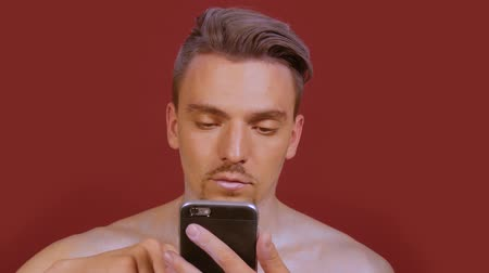 burgundia : Stylish smiling guy uses a phone and looks right into the frame on a burgundy background. A portrait of young man winks with smartphone and a bright make-up