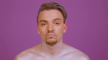 compleição : Stylish guy looks straight into the frame on a purple background and leaves after raising the background. A young man with bright makeup finished shooting Stock Footage