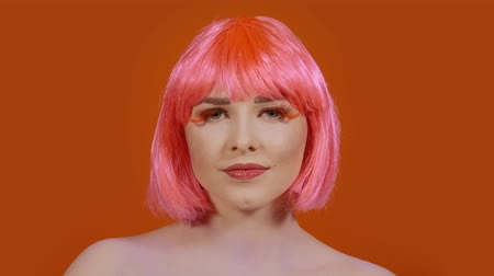 актер : Stylish young woman looks directly into the frame on an orange background. A girl with a bright make-up and red-pink hair Стоковые видеозаписи