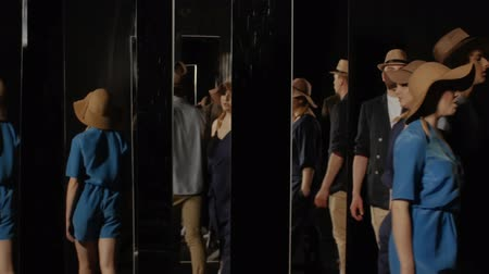 голос : Group of young people randomly walking around the room through the mirrors. Company of singers on a black background with mirrors. Concept of space and time Стоковые видеозаписи