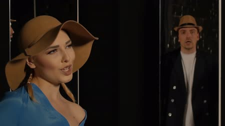 vokální : Young woman in a hat sings on a black background with a mirrors where the guy is reflected. Girl singer emotionally performs lyrical vocals