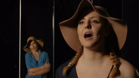 musician : Stylish young women in a hat sing on a black background with a mirrors where the woman is reflected. Girl singer emotionally performs lyrical vocals Stock Footage