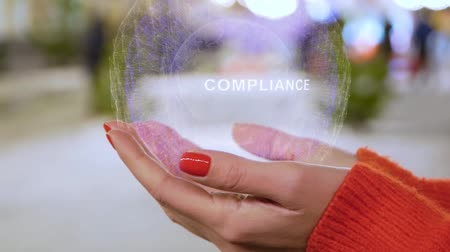 megfelel : Female hands holding a conceptual hologram with text Compliance. Woman with red nails and sweater with future holographic technology on a blurred background of the street