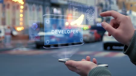 fejlesztése : Female hands on the street interact with a HUD hologram with text Developer. Woman uses the holographic technology of the future in the smartphone screen on the background of the evening city