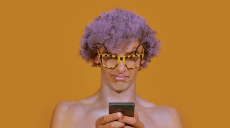 calabrone : Curly stylish guy in funny glasses uses a phone, looks directly into the frame and smiles on a color orange background. Portrait of a young man looks like a bee or a hornet