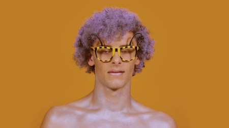 calabrone : Curly stylish guy in funny glasses waving his head fun on a color orange background. A portrait of a young man looks like a bee or a hornet