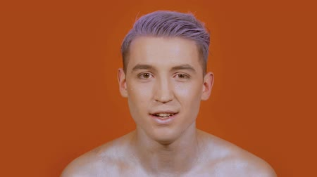 vokální : Stylish guy vocalist looks right into the frame on an orange background. The young man performs the vocals emotionally Dostupné videozáznamy