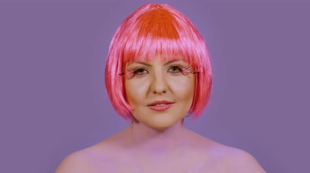 vokální : Stylish young woman back vocalist sings la la la and looks directly into the frame on a violet background. A girl with a bright make-up and red-pink hair performs vocals emotionally Dostupné videozáznamy