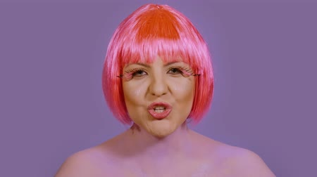 vokální : Stylish young woman vocalist sings and looks directly into the frame on a violet background. A girl with a bright make-up and red-pink hair performs vocals emotionally