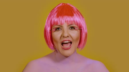 vokální : Stylish young woman vocalist sings and looks directly into the frame on a yellow background. A girl with a bright make-up and red-pink hair performs vocals emotionally