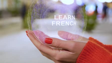 dicionário : Female hands holding a conceptual hologram with text Learn French. Woman with red nails and sweater with future holographic technology on a blurred background of the street