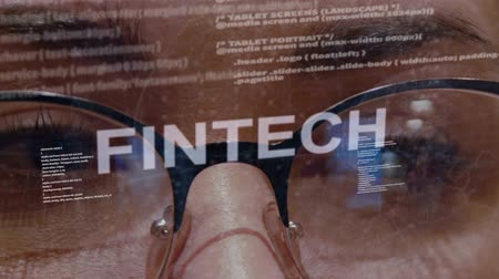 fintech : Fintech text on the background of female software developer. Eyes of woman with glasses are looking at programming network code space abstract technologies connecting global data network Stock Footage