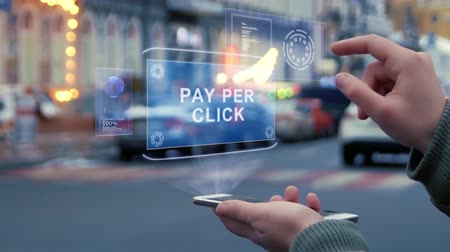 implementation : Female hands on the street interact with a HUD hologram with text Pay per click. Woman uses the holographic technology of the future in the smartphone screen on the background of the evening city