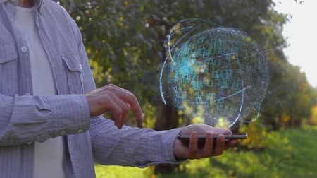 возвращение : Unrecognizable man shows conceptual hologram with text ROI. Farmer on the background of the apple orchard in casual clothes with the technology of the future mobile screen