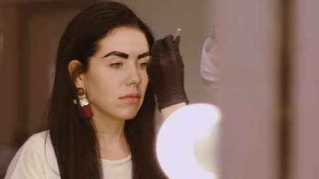 prosedür : Cosmetologist apply paint with brush on the eyebrows of a beautiful patient. Part of eyebrow correction procedure. Professional care for face in beauty saloon Stok Video