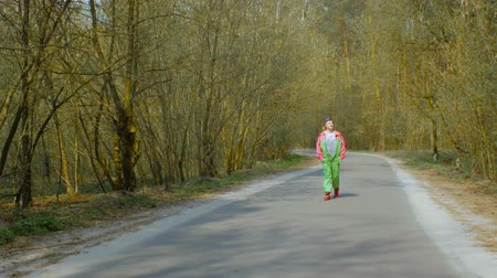 sem camisa : Young woman in a ski suit is walking along the road in the forest. Girl dreams of winter and snow in summer day