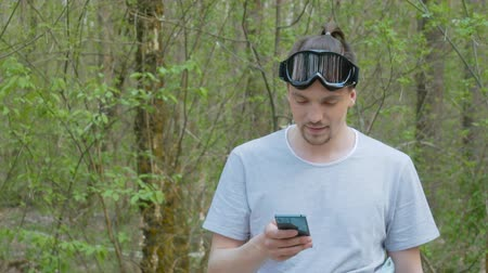 skier : Portrait of a happy smiling bearded man using a phone in the forest. Attractive guy with beard wearing a t-shirt and ski goggles on a background of nature Stock Footage