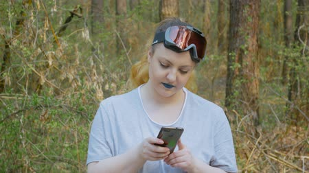 viajero : Portrait of a happy woman with blue lipstick using a phone in the forest. Blonde wearing a t-shirt and ski goggles on a background of nature Archivo de Video