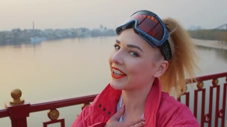 hajtások : Blonde young woman blogger in ski goggles, standing on the waterfront of the city, shoots a video blog or video call. The girl in the pink jacket shoots vlog on camera at sunset. Slowmotion