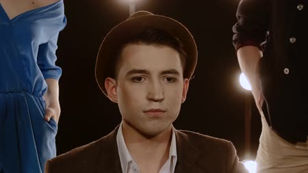 vokální : Attractive guy vocalist in a jacket and hat, against a background of bright lights. Closeup portrait of a young man performs the vocals emotionally