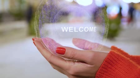 cíle : Female hands holding a conceptual hologram with text Welcome. Woman with red nails and sweater with future holographic technology on a blurred background of the street