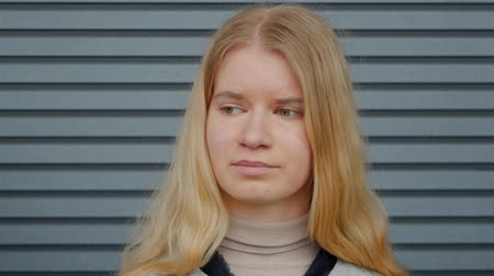 gestreept : Portrait of a young blonde woman looking around and after cheerfully smiling looking at the camera against the background of a striped wall. Girl student with a central heterochromia close-up Stockvideo