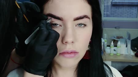 хозяин : Cosmetologists hand pulls out the beautiful patients eyebrow with a pair of tweezers. Part of the eyebrow correction procedure. Professional face care in a beauty salon
