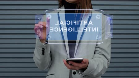 displays : Unrecognizable business woman, interacts with a HUD hologram Artificial Intelligence. Girl in a business suit uses the technology of the future mobile screen against the background of a striped wall
