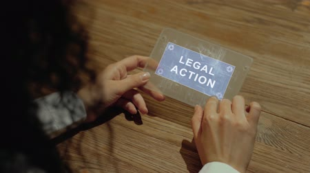 self defence : Unrecognizable woman working on a futuristic tablet with a hologram text Legal action. Womens hands with future holographic technology at a wooden table Filmati Stock