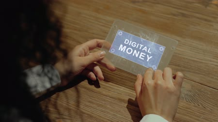data mining : Unrecognizable woman working on a futuristic tablet with a hologram text Digital money. Womens hands with future holographic technology at a wooden table Stock Footage