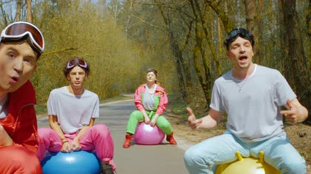 freeride : Movement through a happy company of friends in bright ski suits sings fun on bright balls on a forest road in sunny weather. Young people musicians in goggles with colorful balls in the forest