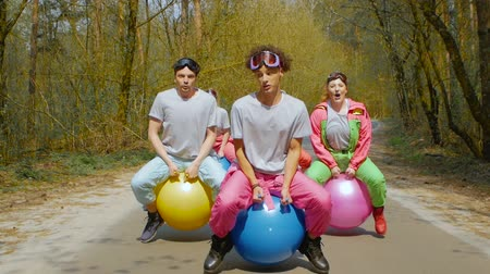 freeride : Cheerful company of friends in colorful ski suits sings fun and jumping on bright balls along a forest road in slow motion. Young people musicians in goggles with colorful balls in the forest