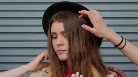bídný : Portrait of a young woman in a hat who is touched by plenty of hands against the background of a striped wall. Sad brunette girl student close up among the palms of hands. Social concept