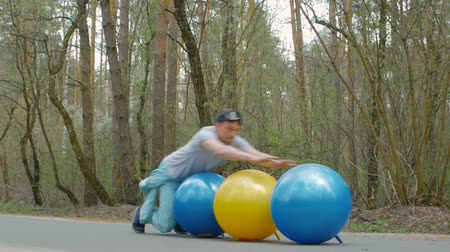 eşofman : Yyoung man in a blue ski suit does stunts on the balls on the road in the forest. Guy athlete is having fun Stok Video