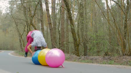eşofman : A young man in a ski suit does stunts on the balls on the road in the forest. Guy athlete is having fun