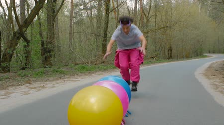 eşofman : Guy athlete is having fun. Young man in a ski suit does stunts on the balls on the road in the forest Stok Video