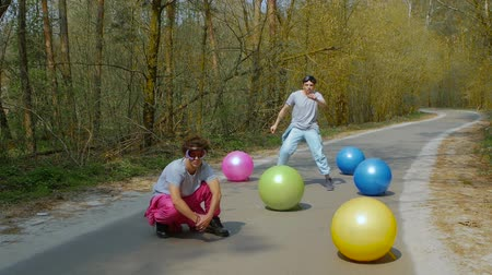 friendship dance : Young men street dancers in goggles with colorful balls in the forest. Slow motion of happy guys in bright ski suits among of bright balls on a forest road