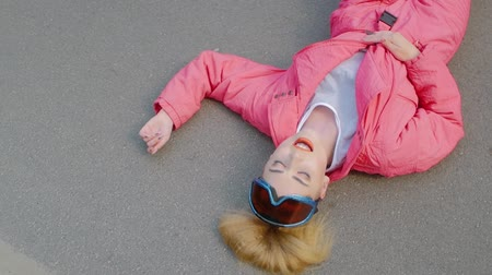 položit : Blonde girl sings, lying on the asphalt road in a pink jacket. Attractive girl wearing ski goggles on the ground background