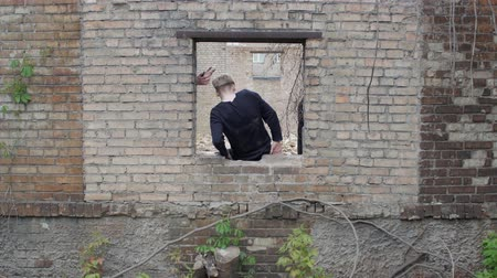 приложение : Guy is trying to get out through a hole in the wall of the post of the apocalypse on the ground. Young people in black climb into the window of a brick wall. Attachment concepts