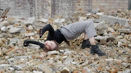 танцоры : Girl in black lies in the ruins of an apocalypse post on the ground, A young woman dancing lying against the background of a collapsed building and scattered bricks