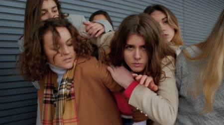 apprehensive : A young woman sneaks through the crowd against a striped wall. Female students infringe upon a girl. Concepts social danger or unfortunate victim