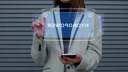 interacts : Unrecognizable business woman, interacts with a HUD hologram with text Hydropower. Girl in a business suit uses the technology of the future mobile screen against the background of a striped wall