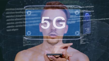 standardization : Young man interacts with a conceptual HUD hologram with text 5G. Guy with future technology mobile screen on background of the program code