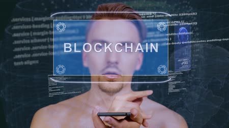 estratégico : Young man interacts with a conceptual HUD hologram with text Blockchain. Guy with future technology mobile screen on background of the program code