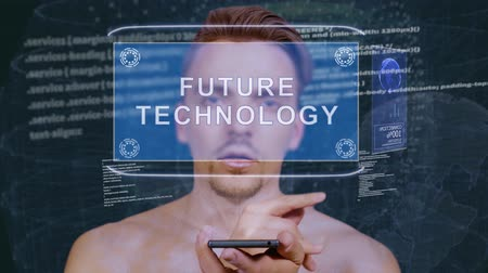 visão global : Young man interacts with a conceptual HUD hologram with text Future technology. Guy with future technology mobile screen on background of the program code