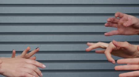 достигать : Many hands are trying to reach out to each other against the background of a striped wall. The concept of unity. Human fingers touch frantically Стоковые видеозаписи