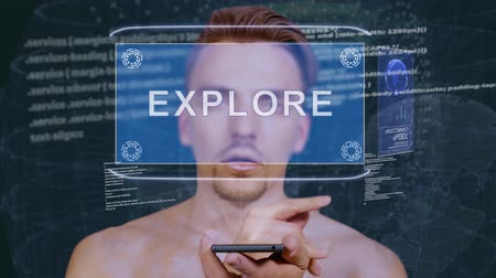 földrajz : Young man interacts with a conceptual HUD hologram with text Explore. Guy with future technology mobile screen on background of the program code
