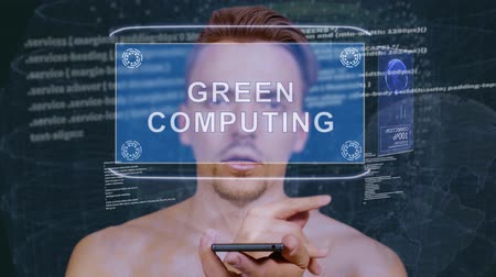 uzun ömürlü : Young man interacts with a conceptual HUD hologram with text Green computing. Guy with future technology mobile screen on background of the program code